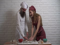 Cheerful girl pours white flour on face her bearded boyfriend in the kitchen. Stock Footage