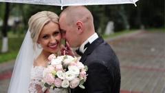 Bride and groom kiss, blocking umbrella Stock Footage