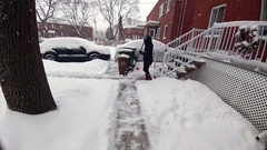 Woman shoveling in a residential area in Montreal Canada Stock Footage