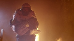 Brave Fireman Descends Stairs of a Burning Building with a Saved Girl in His Arm Stock Footage