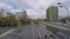 Bicyclists crowd ride by Jauza river quay with transport traffic Stock Footage