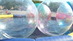Child inside big inflatable ball on water surface Stock Footage