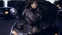 Young girl frustrated waiting for help beside broken car with open hood talking Stock Footage