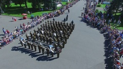 Military orchestra play music and start march among spectators on alley Stock Footage