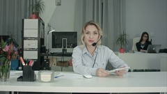 Smiling call center agent using tablet and talking to the camera Stock Footage