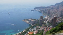 Monte Carlo, Monaco, Vessels sail near coastal city with street traffic Stock Footage