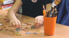 Children play intellectual game collecting puzzles Stock Footage