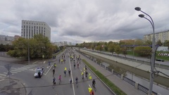 Many bicyclists ride by Yauza river quay with transport traffic Stock Footage