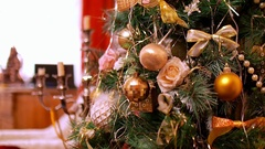 Close-up of gold Christmas balls hanging on artificial fir. On blurred Stock Footage