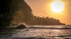 Local Kids surf on Waves in Sunset light, Beautiful Crystal Bay, Nusa Penid.. Stock Photos