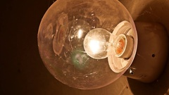 Light bulb in a glass bell hanging on the wall, night light lamp Stock Footage