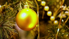Close-up of gold Christmas balls hanging on artificial fir. Flashing yellow Stock Footage