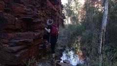Girl climbing along red rock ledge in Karijini NP Stock Footage