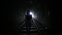 Mysterious woman walking in dark tunnel. Female silhouette on light background Stock Footage
