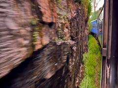 Moving passenger train passing sharp cliffs during traveling in Sri Lanka Stock Footage