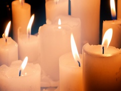 Many burning light wax candles with waving yellow flame on black background Stock Footage