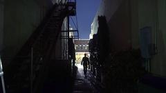 Woman walks toward camera from dark alley 4k Stock Footage