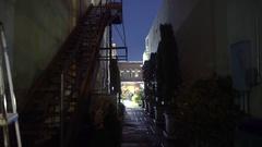 Woman walks past camera into a dark alley 4k Stock Footage
