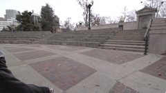 A young man freerunner doing parkour and running in a city courtyard, super slow Stock Footage