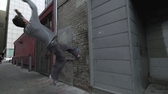 A young man freerunner doing parkour and flips off a wall in an alley. Stock Footage