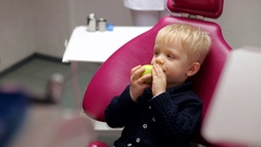Small child sitting in the dental chair and eating a green apple. Stock Footage