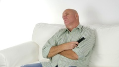 Tired Person Sleeping at Home Sitting on the Bed Front of TV with RC in Hand. Stock Footage