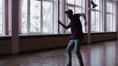 A female breakdancer performing in dance studio, dark silhouette of dancing girl Stock Footage