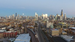 Evening View of City Skyline with moon at sunset and Passenger Train Leaving Stock Footage