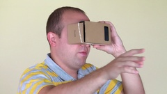 Man walking forward with vr virtual reality cardboard glasses Stock Footage