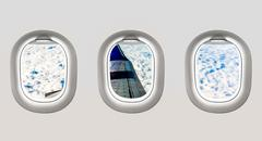 Looking out the windows of a plane to the aircraft wing and clou Stock Photos