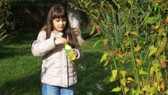 Beautiful little girl playing with soap bubbles in the garden. Stock Footage