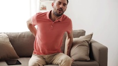 Unhappy man suffering from backache at home Stock Footage