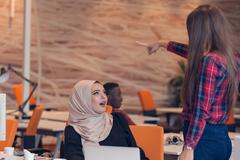 Arabic businesswoman wearing hijab receiving notification from a colleague Stock Photos