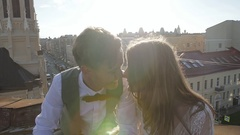 Happy young beautiful stylish couple bride and groom kiss gently on the roof at Stock Footage