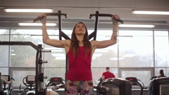 Working out in a sport club. Young sporty woman is doing pull-ups on sport Stock Footage