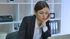 Bored office worker at desk staring at computer screen with hand on chin Stock Footage