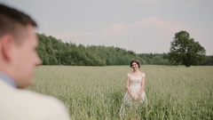Back view of a groom coming up to his beautiful bride in a wheat field on their Stock Footage