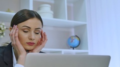 Tired businesswoman having a headache while working on her laptop in bright Stock Footage
