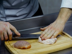 Cutting meat with a knife on a wooden board Stock Footage