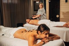 Beautiful woman enjoying a hot stone massage Kuvituskuvat