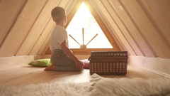 Boy sits in the attic and waves his hand to someone through the window Stock Footage