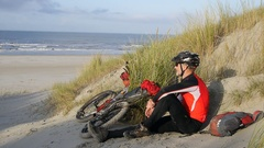 A man resting on the beach by his mountain bike. Stock Footage