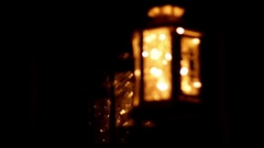 Rack focus shot of a decorative lantern with lights by a window Stock Footage