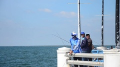 Thai men standing and fishing or angling in sea at Bang Saen Beach Stock Footage