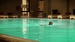 Young girl swims in the indoor pool of a big hotel Stock Footage