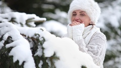 Young woman in the snowy forest warms her fingers and smiles Stock Footage