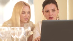 Two attractive young girls sit at the laptop discussing with enthusiasm Stock Footage