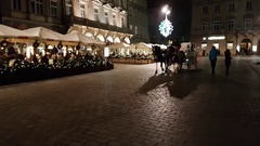 Tourists ride on a carriage around Christmas market at main square in old city Stock Footage