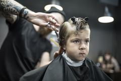 Haircut of small boy in barbershop Stock Photos