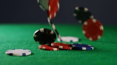 4K Colorful poker chips falling onto green felt, in slow motion Stock Footage
